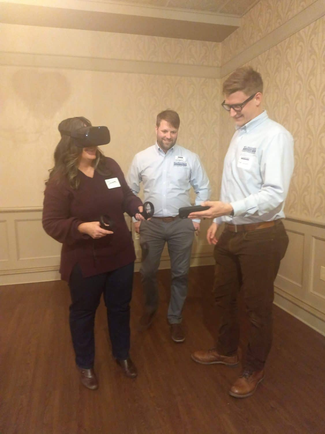 Derek Mulch, AIA, and Matt Sudaholc, PE, with an attendee wearing the VR headset.